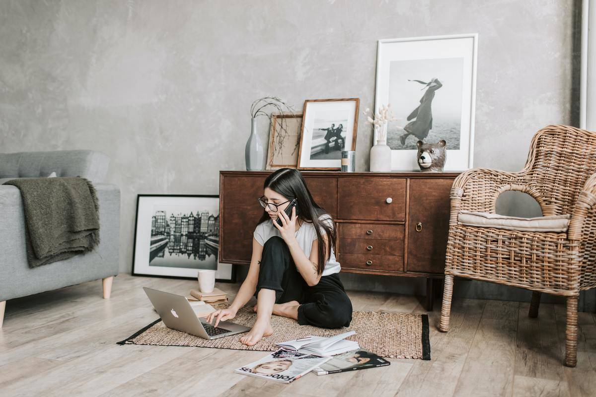 woman sitting on her floor on phone while typing on laptop