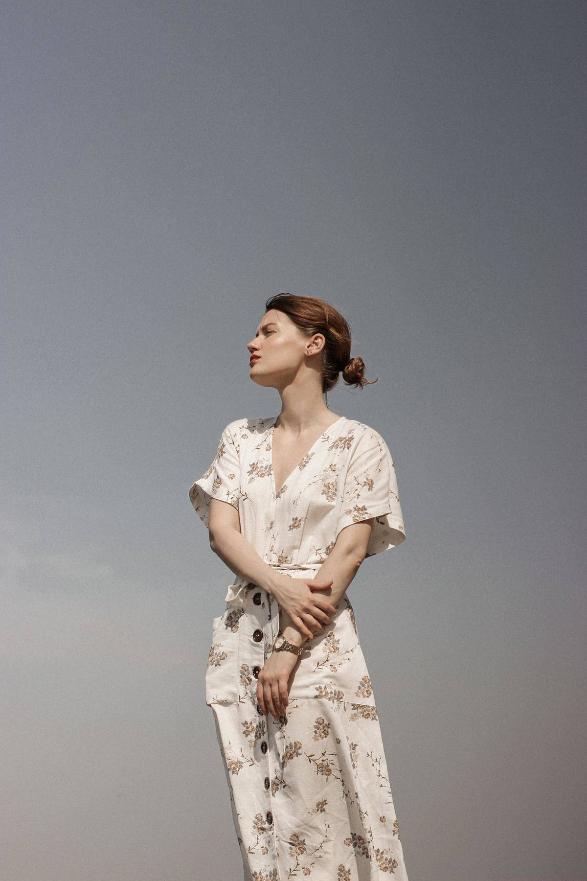 a woman in a flower dress standing looking in the distance