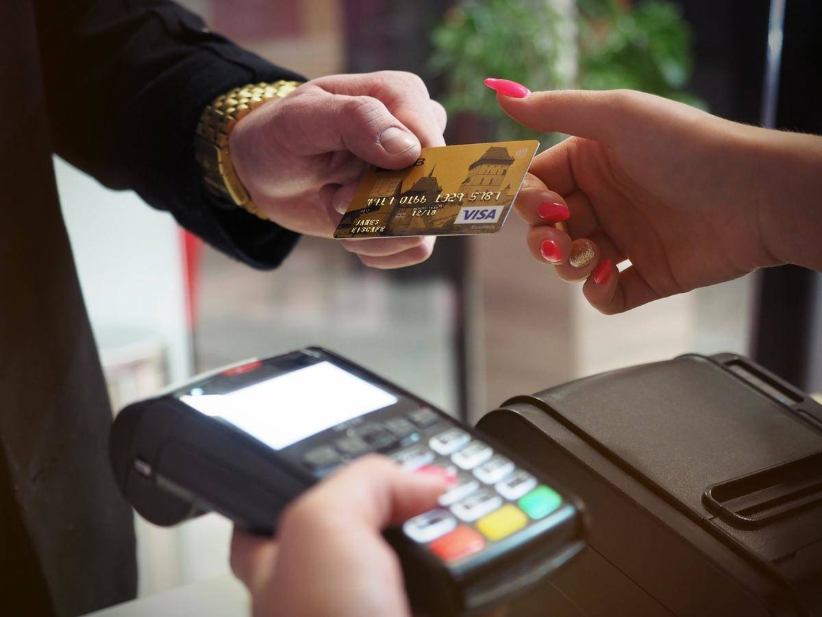 handing credit card to woman with long pink nails
