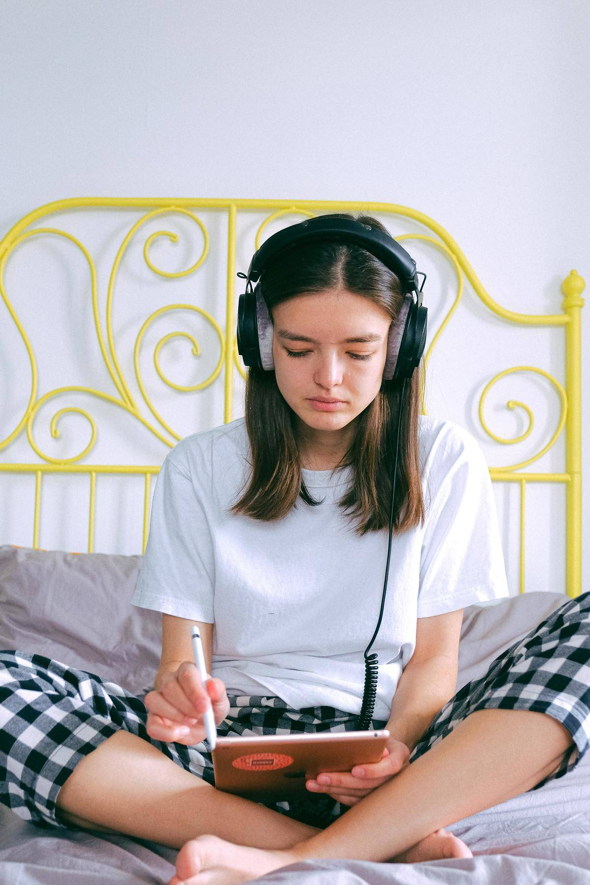 woman with headphones on sitting on a bed, working on an iPad