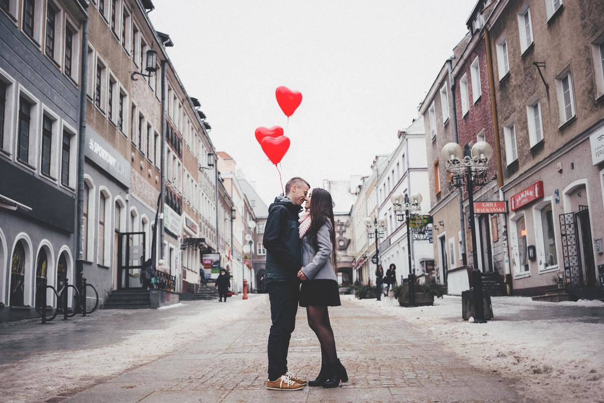 couple standing in the street kissing holding heart balloons