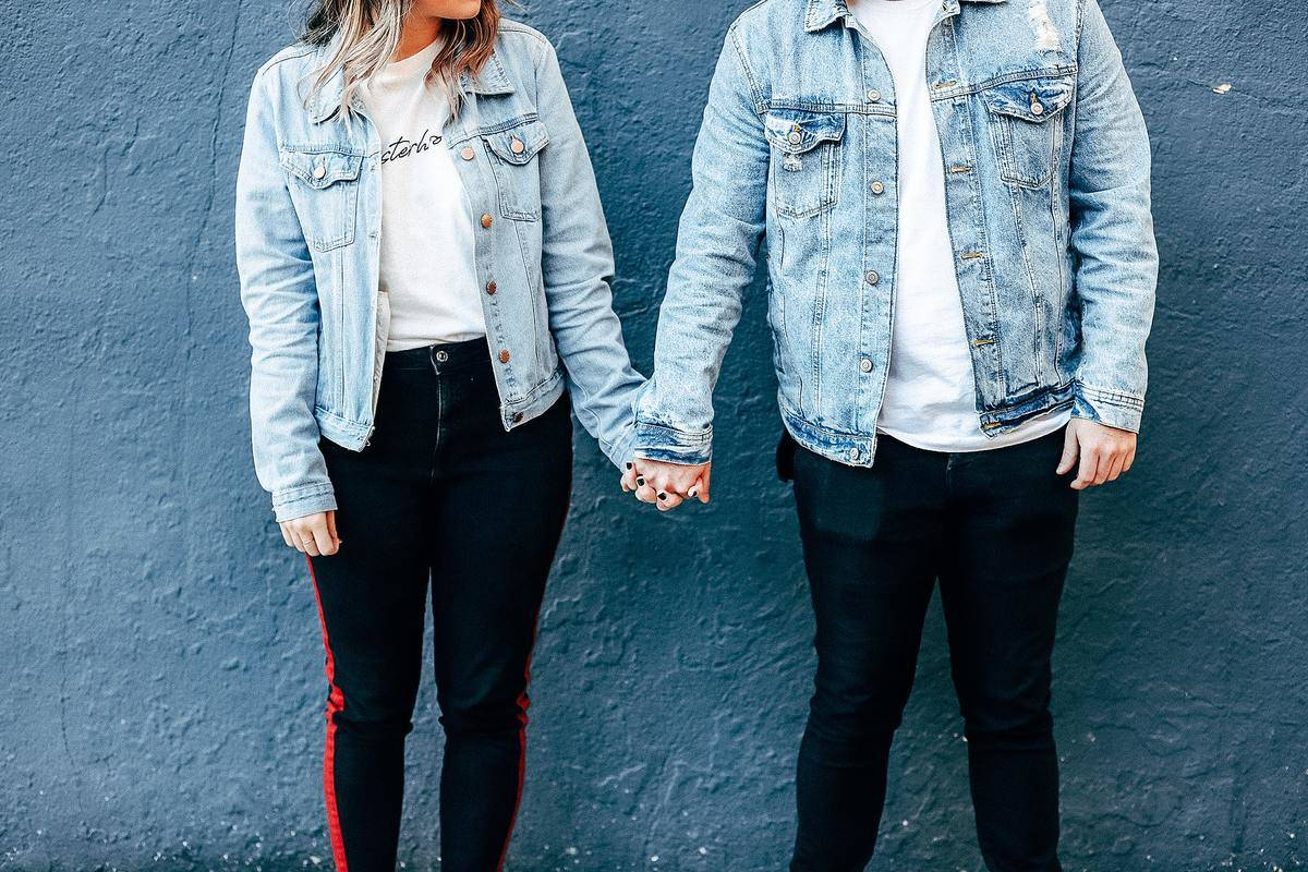 a couple holding hands wearing matching outfits of black pants, white shirt and jean jacket.
