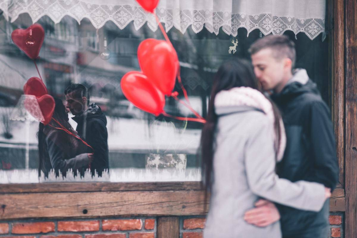 couple kissing while red heart balloons fly in wind behind them