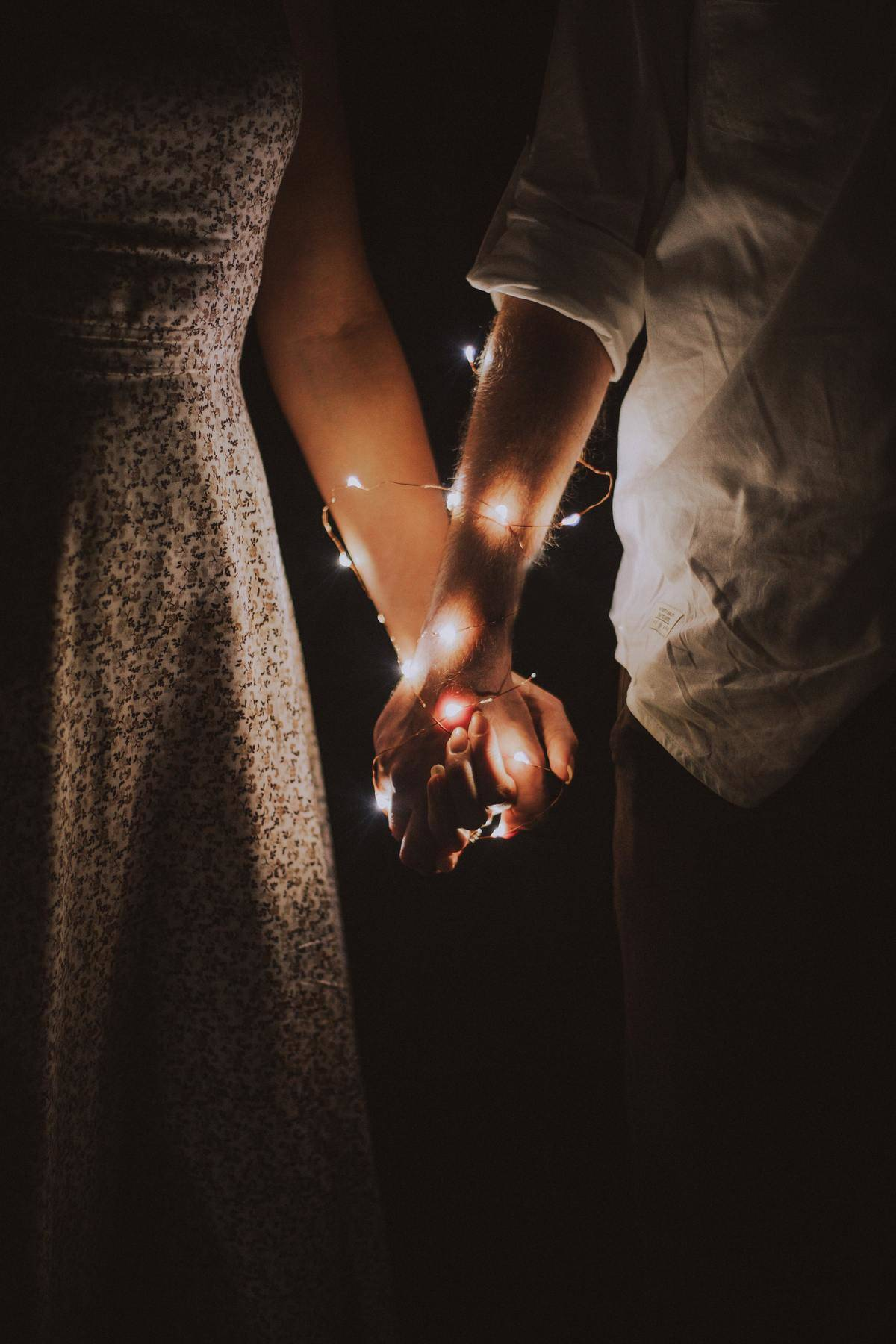 couple holding hands with string lights wrapped around their intertwined hands
