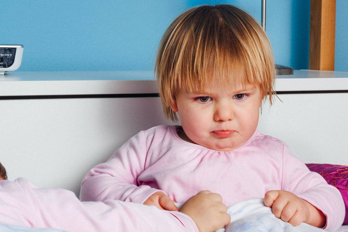 little girl in pink shirt looking upset with fists clenched