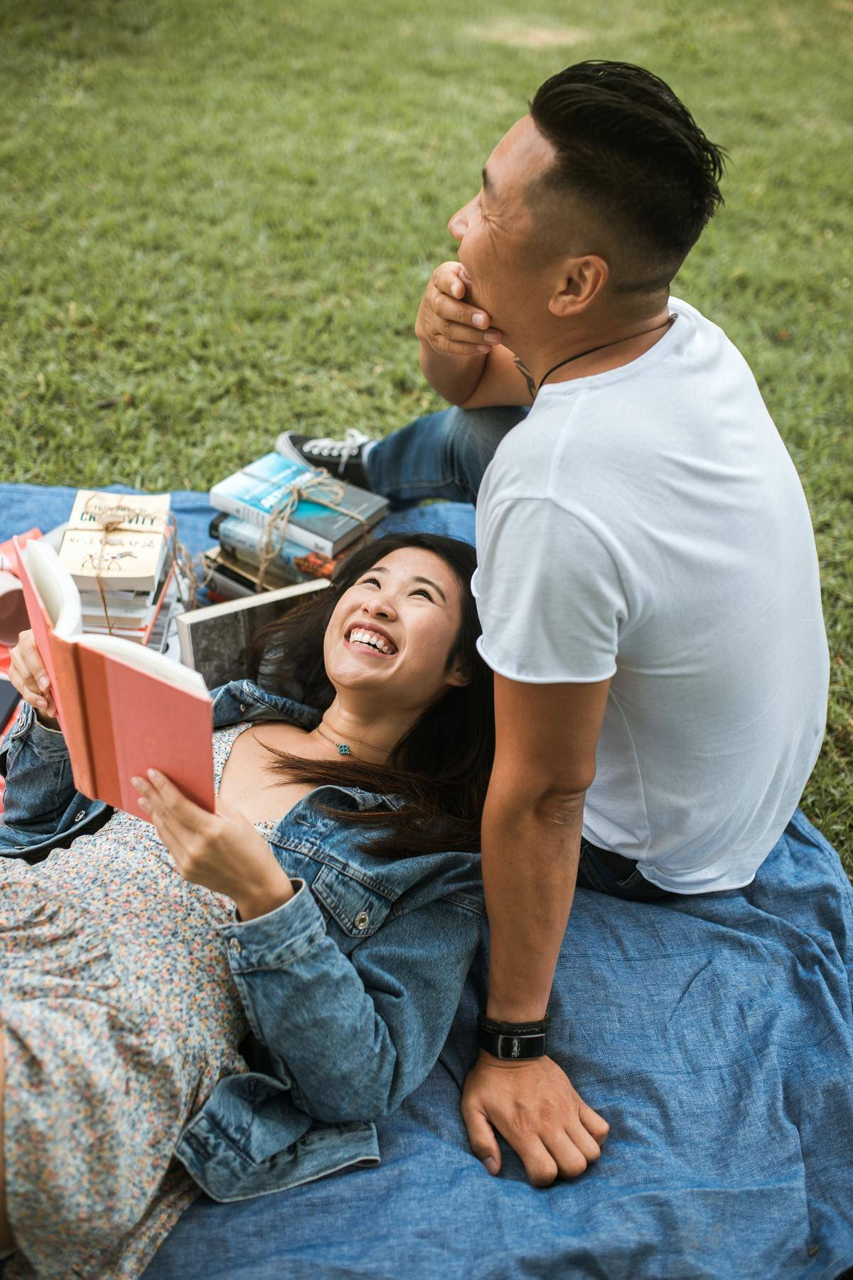 couple on a blanket on grass reading