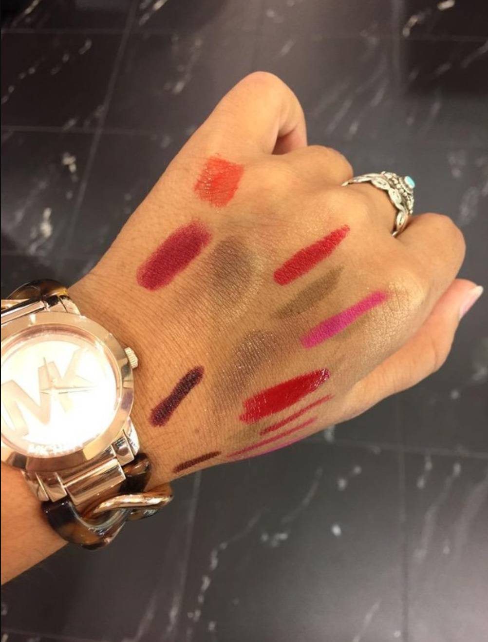 woman with a bunch of makeup tests on her hand