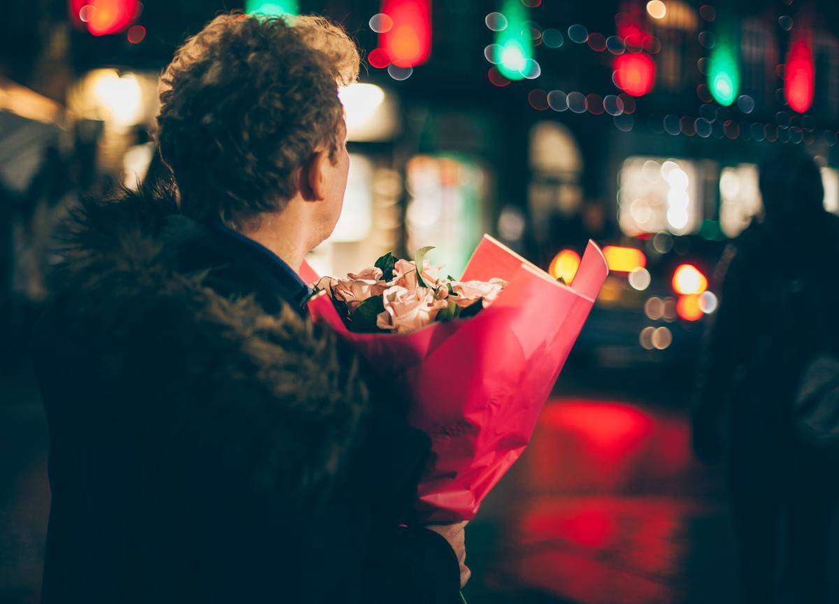 man holds bouquet In night street
