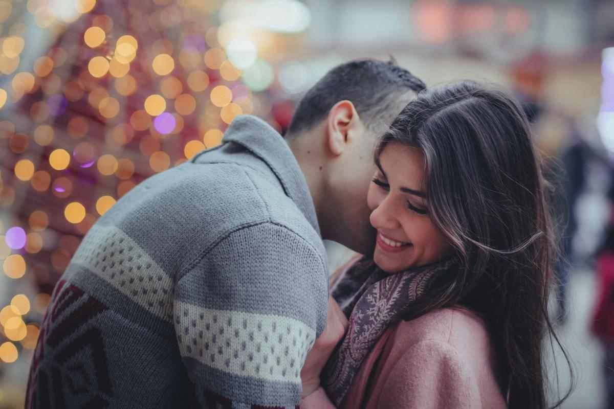 man kisses woman on the cheek by Christmas tree