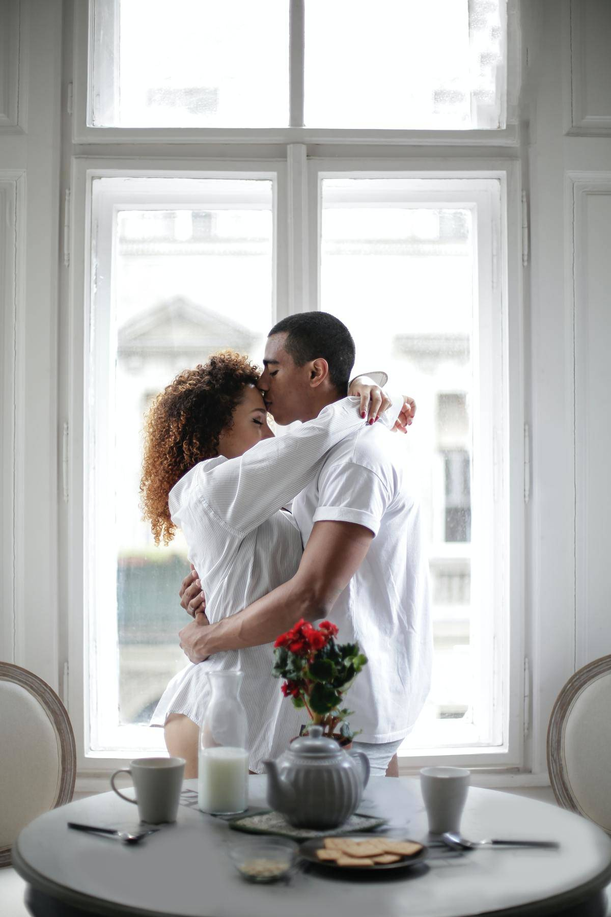 man kisses woman on the forehead by the window
