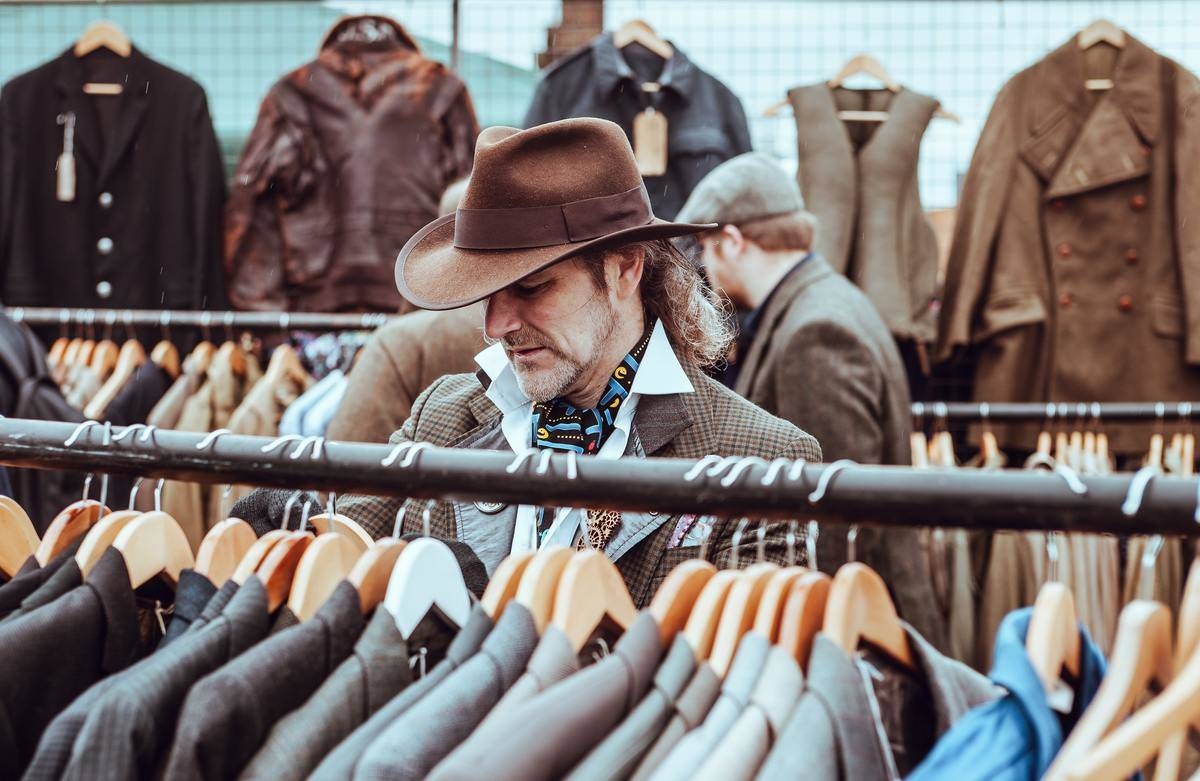 man browsing suits with cowboy hat