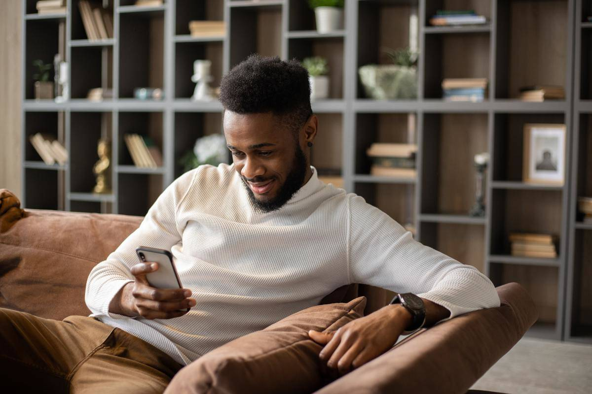 man smiles at his phone while sitting on the couch
