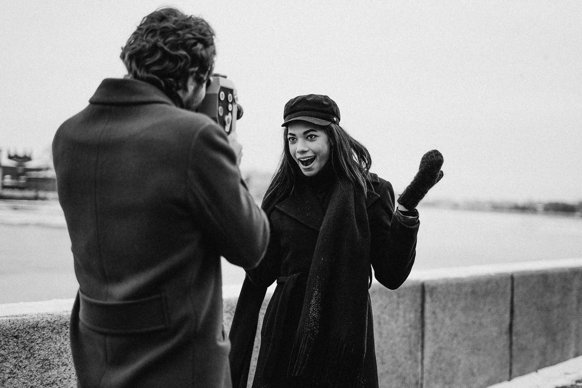 grayscale photo man taking photo of woman smiling in winter coat and hat