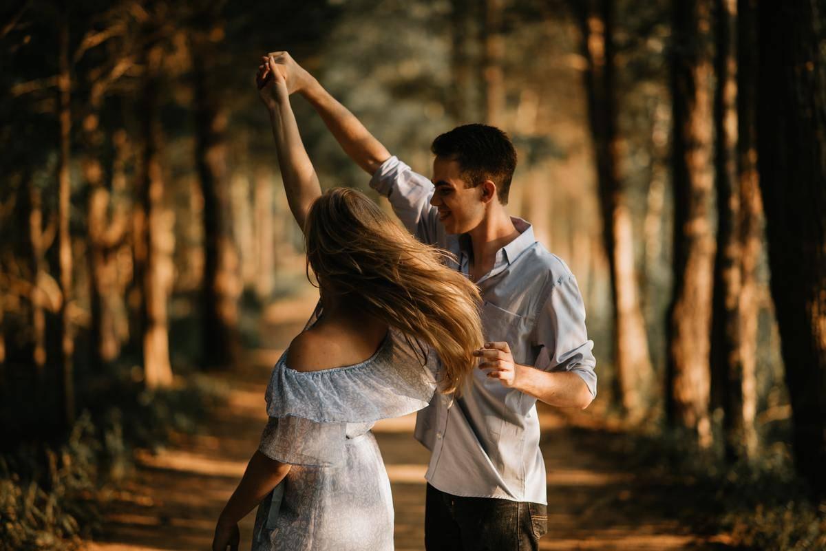 man twirls woman in the woods