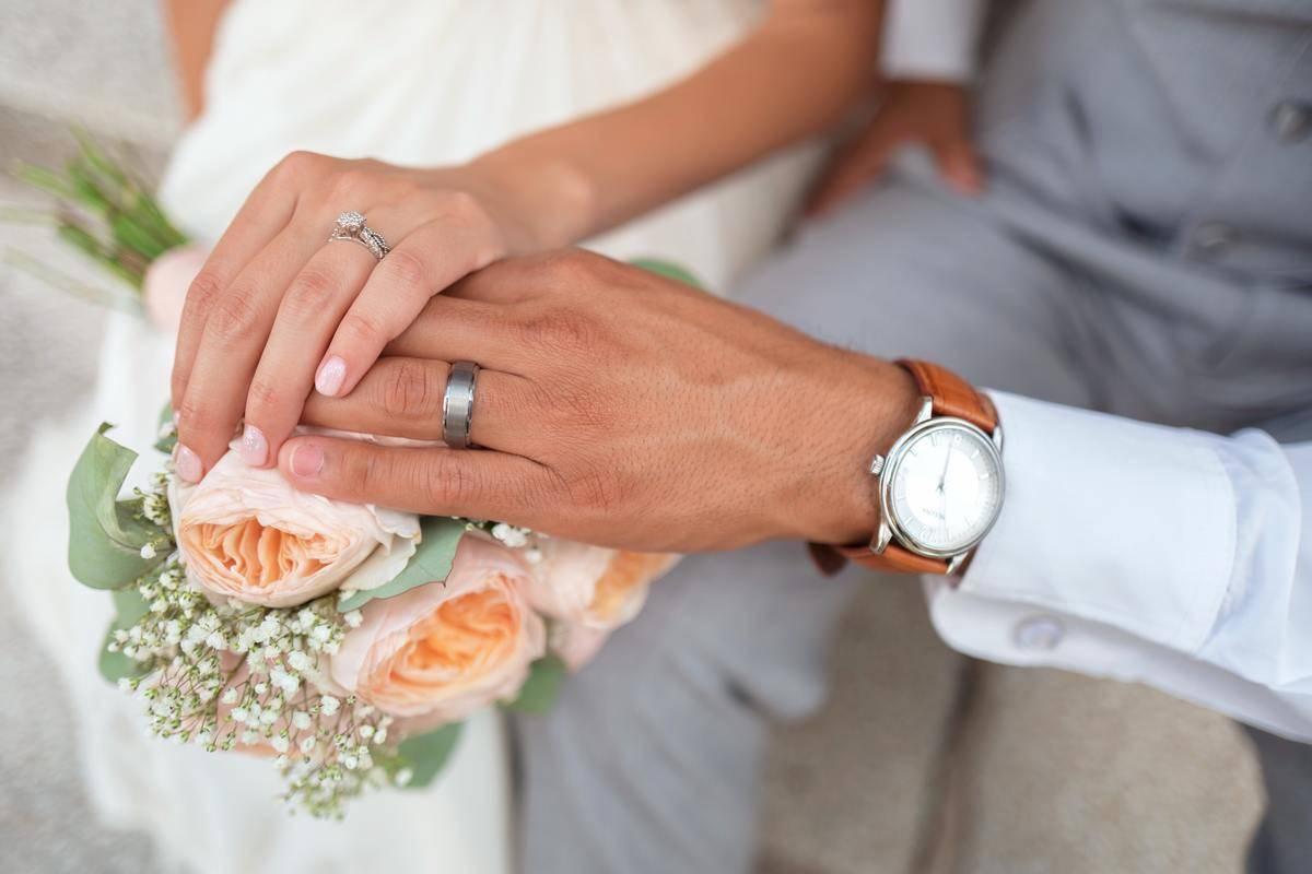 bride and groom display their wedding rings