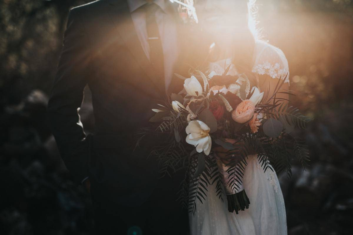 bride and groom stand in sunlight