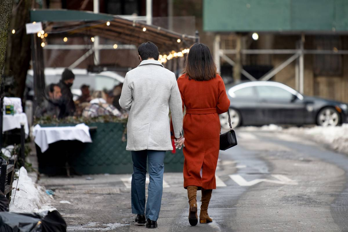 A couple wearing gloves holds hands while walking in the West Village on Valentine's Day on February 14, 2021