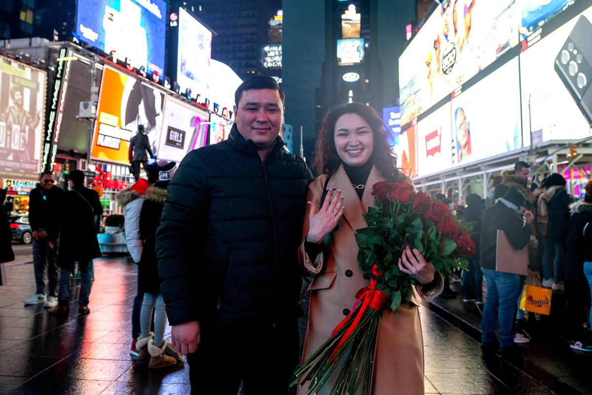 Daniyr Makulbekov and Elmira Baigaskina, visiting from Kazakhstan, pose together after getting engaged in Times Square on Valentine's Day
