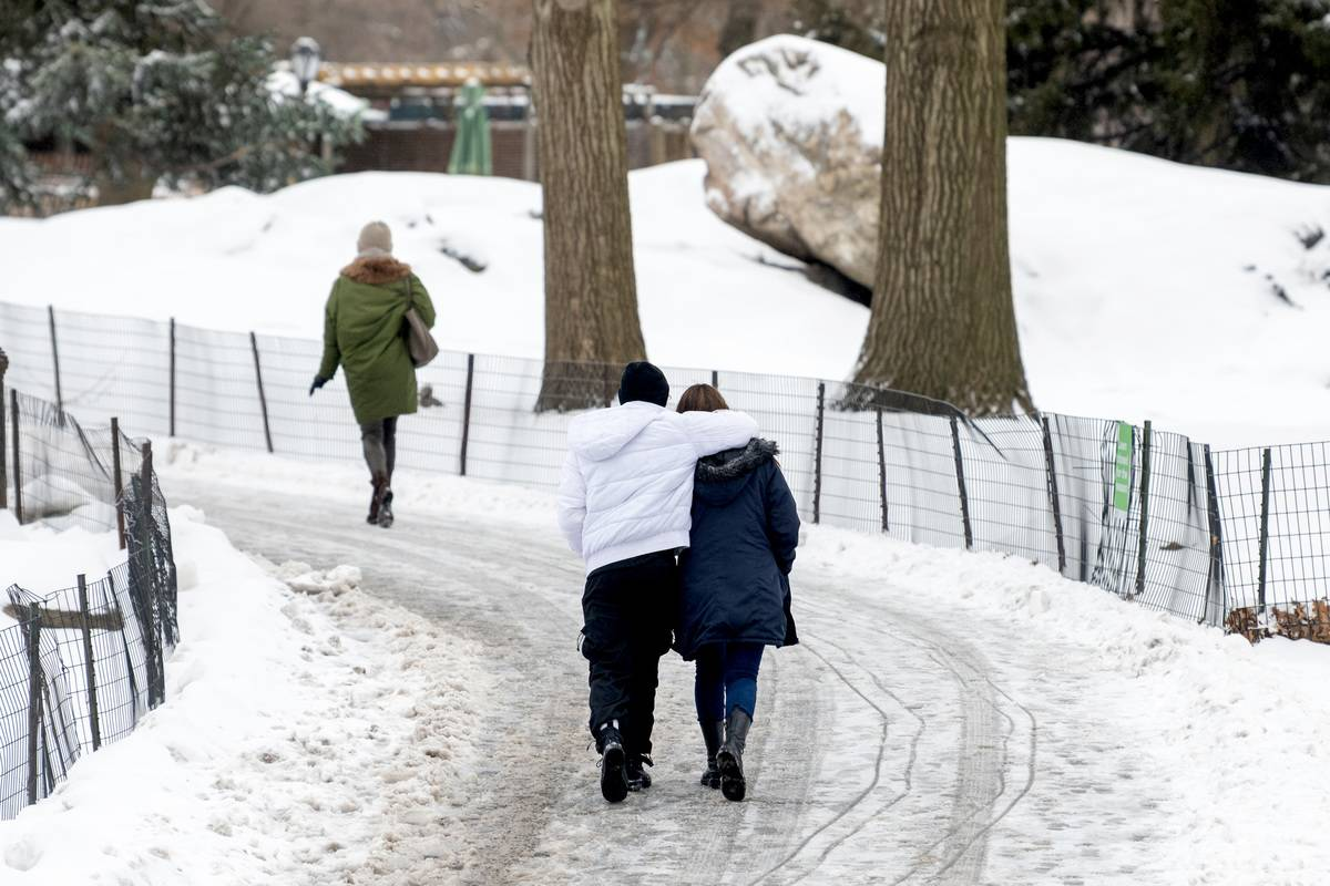 : A couple walks arm and arm during a snow storm in Central Park on February 18, 2021 in New York City