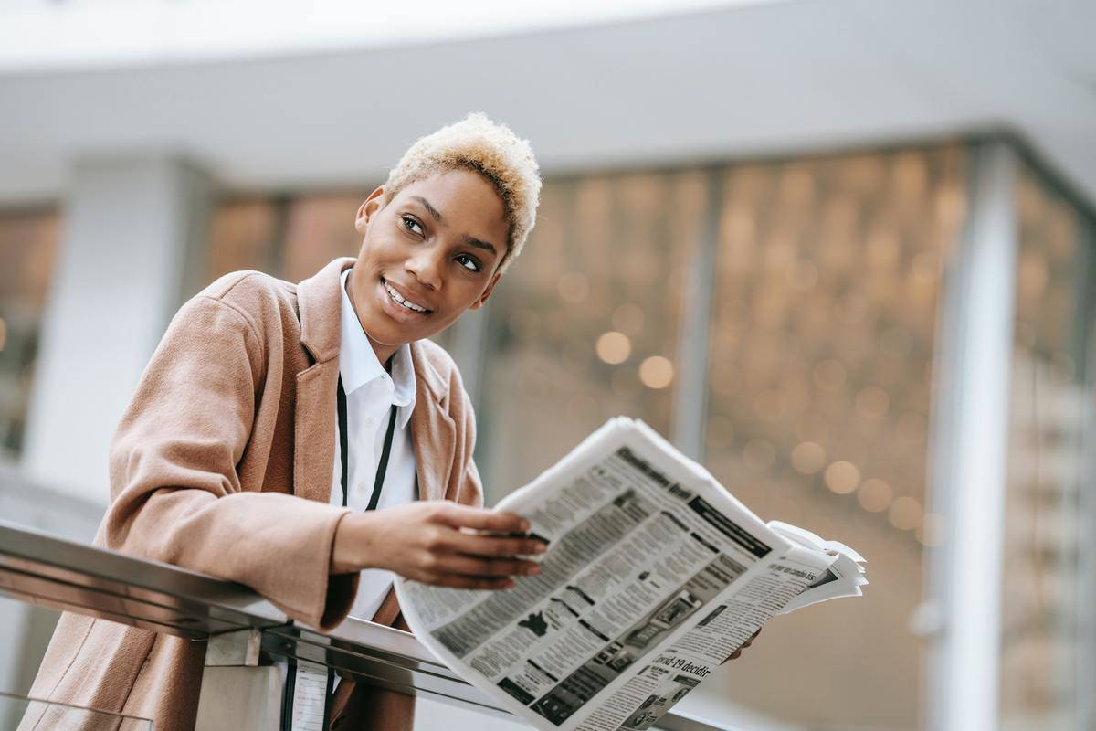 woman looking at a newspaper