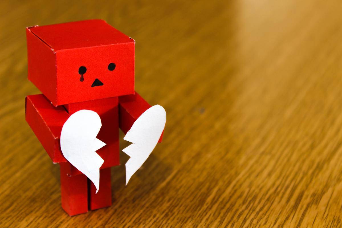 paper robot holds paper heart that's split in two