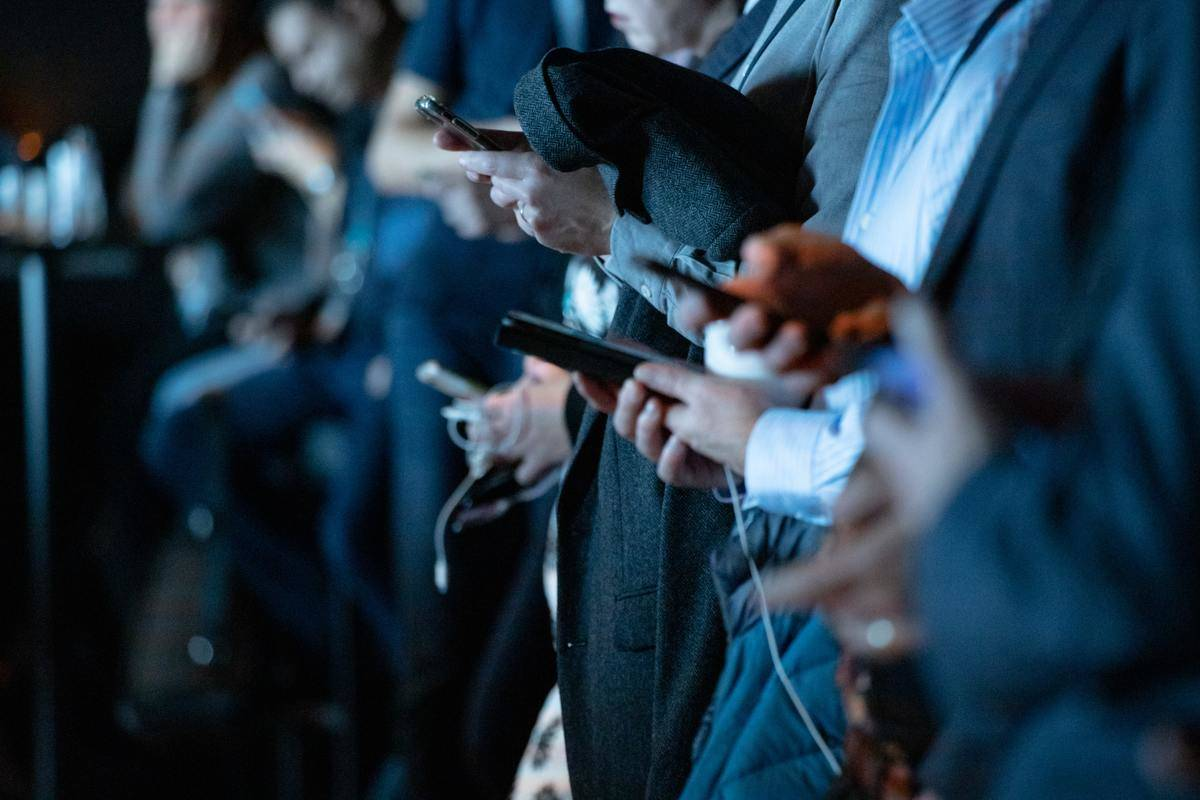 people on their phones in a line