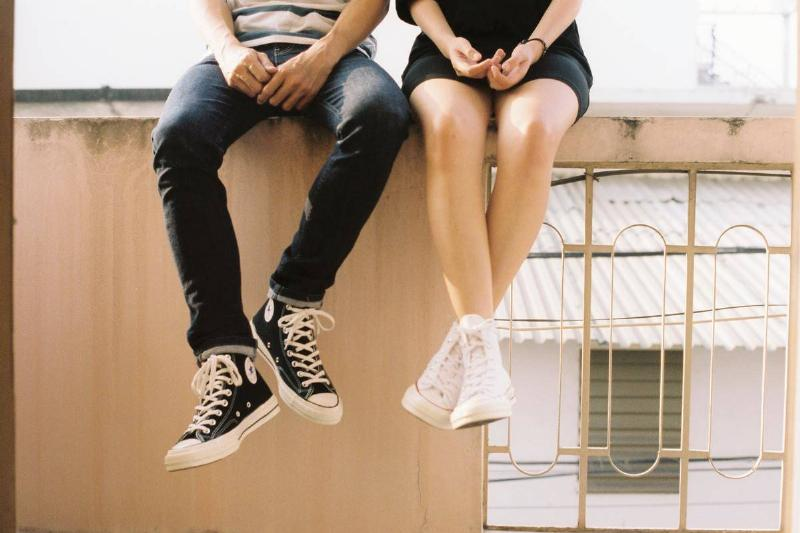 couple sitting on wall, only their legs and hands visible