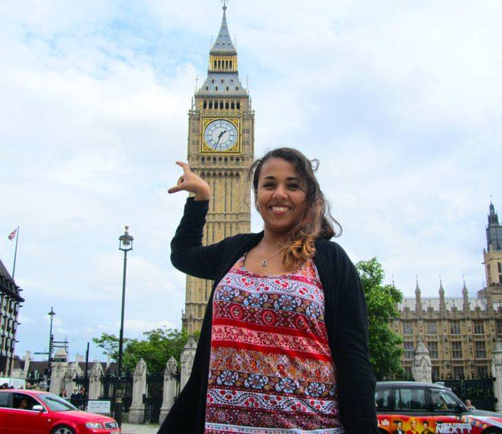 young woman trying to take photo holding big ben