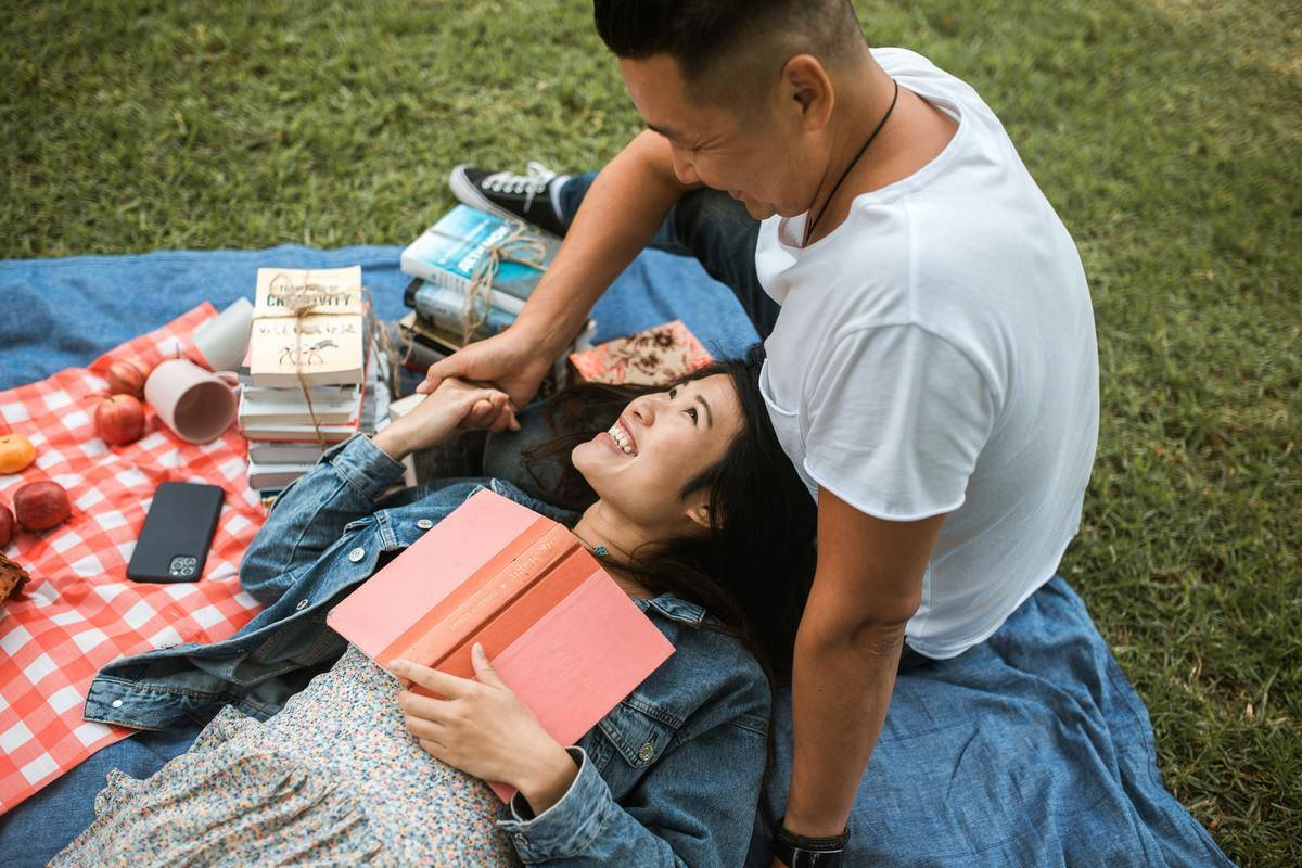 a couple on a picnic. she's lying on his lap with a book on her chest smiling at him