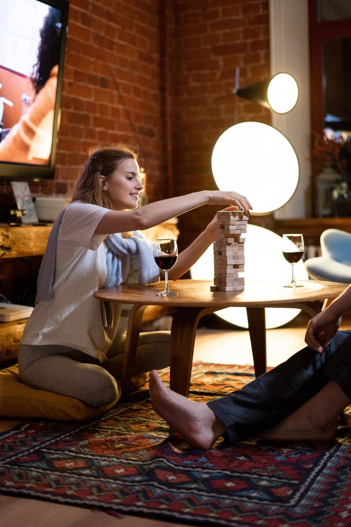 couple sitting on a rug playing Jenga and drinking some wine