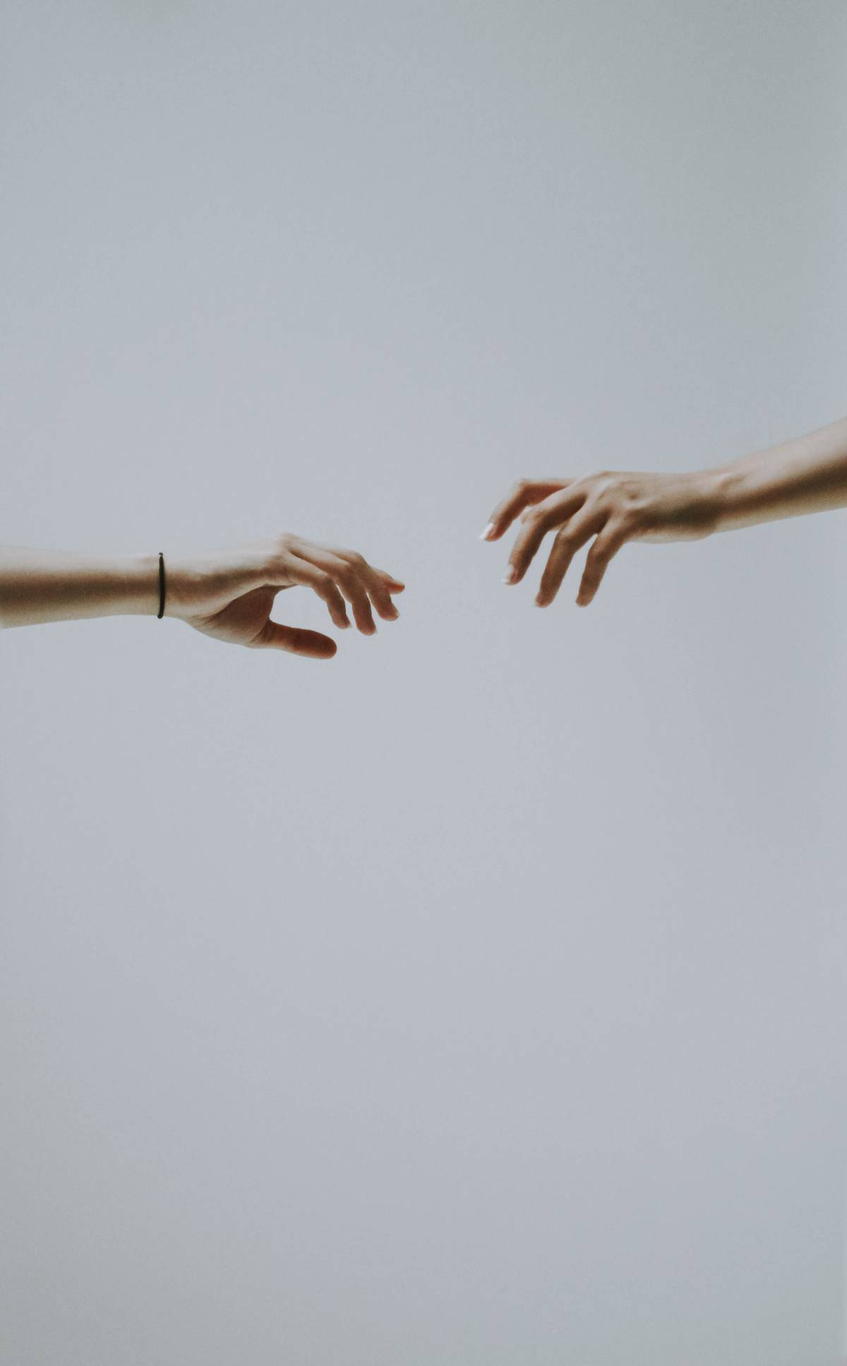 two hands reaching for one another