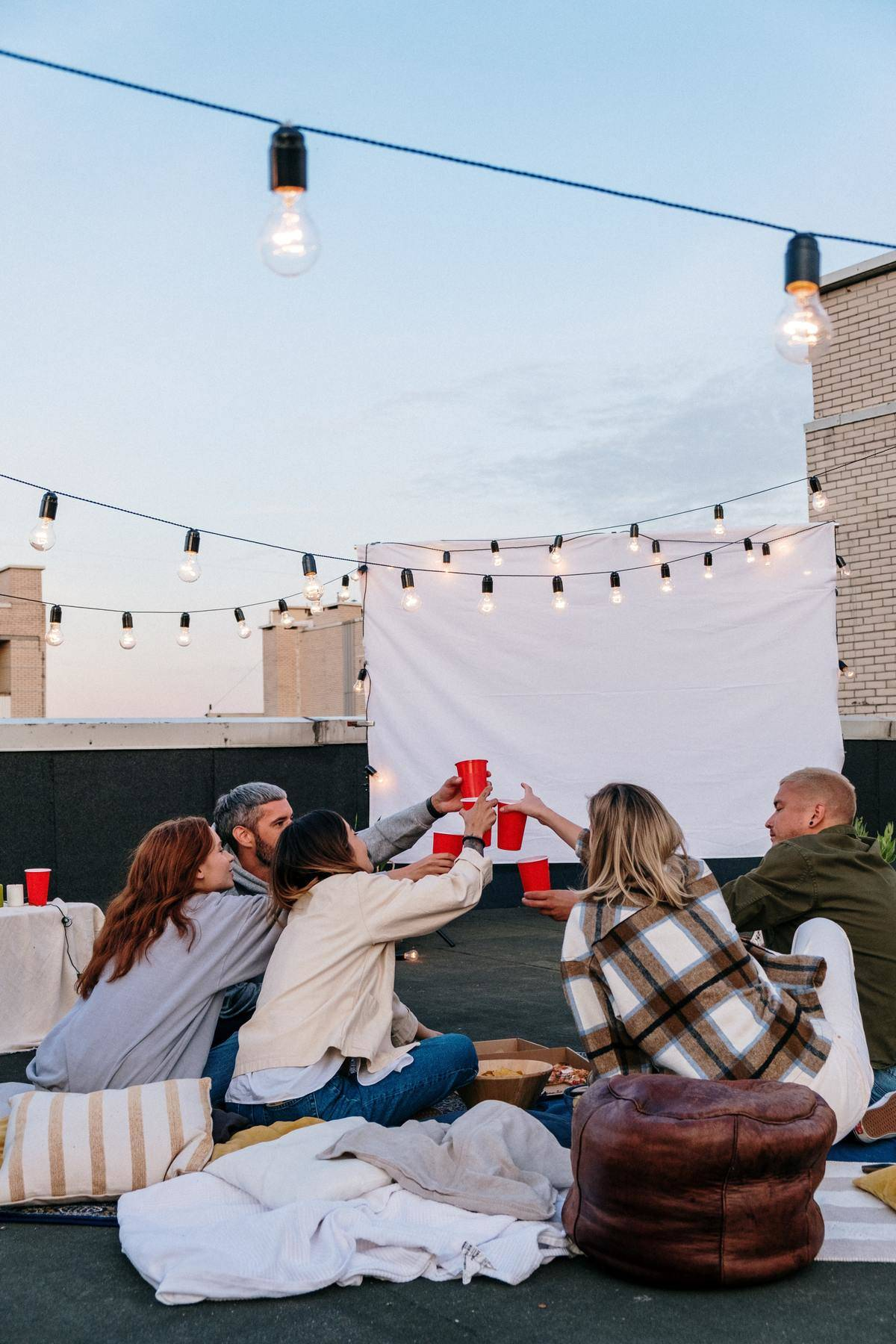 a group of friends on a rooftop cheersing with red solo cups