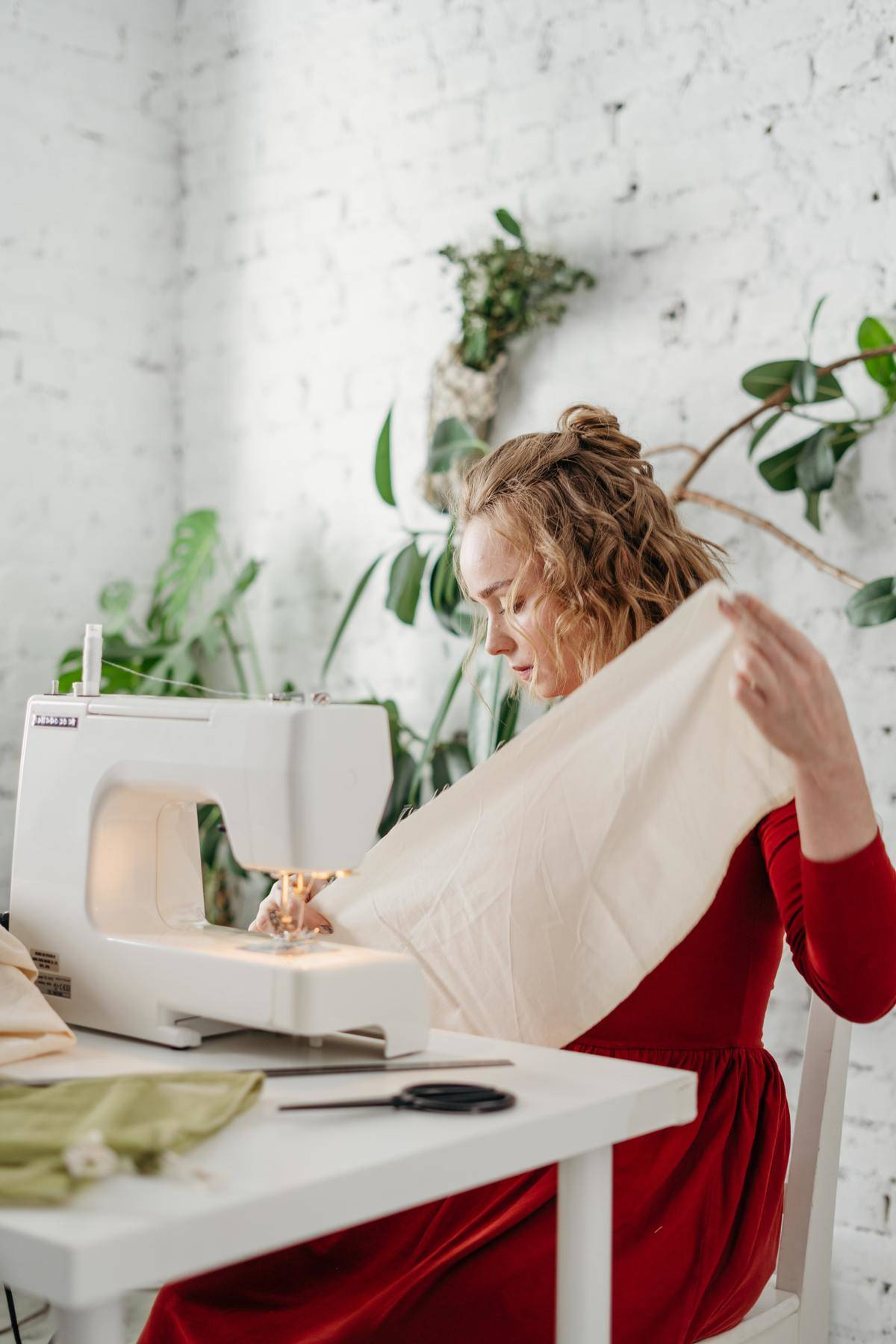 a woman sitting with a sewing machine making something out of white fabric