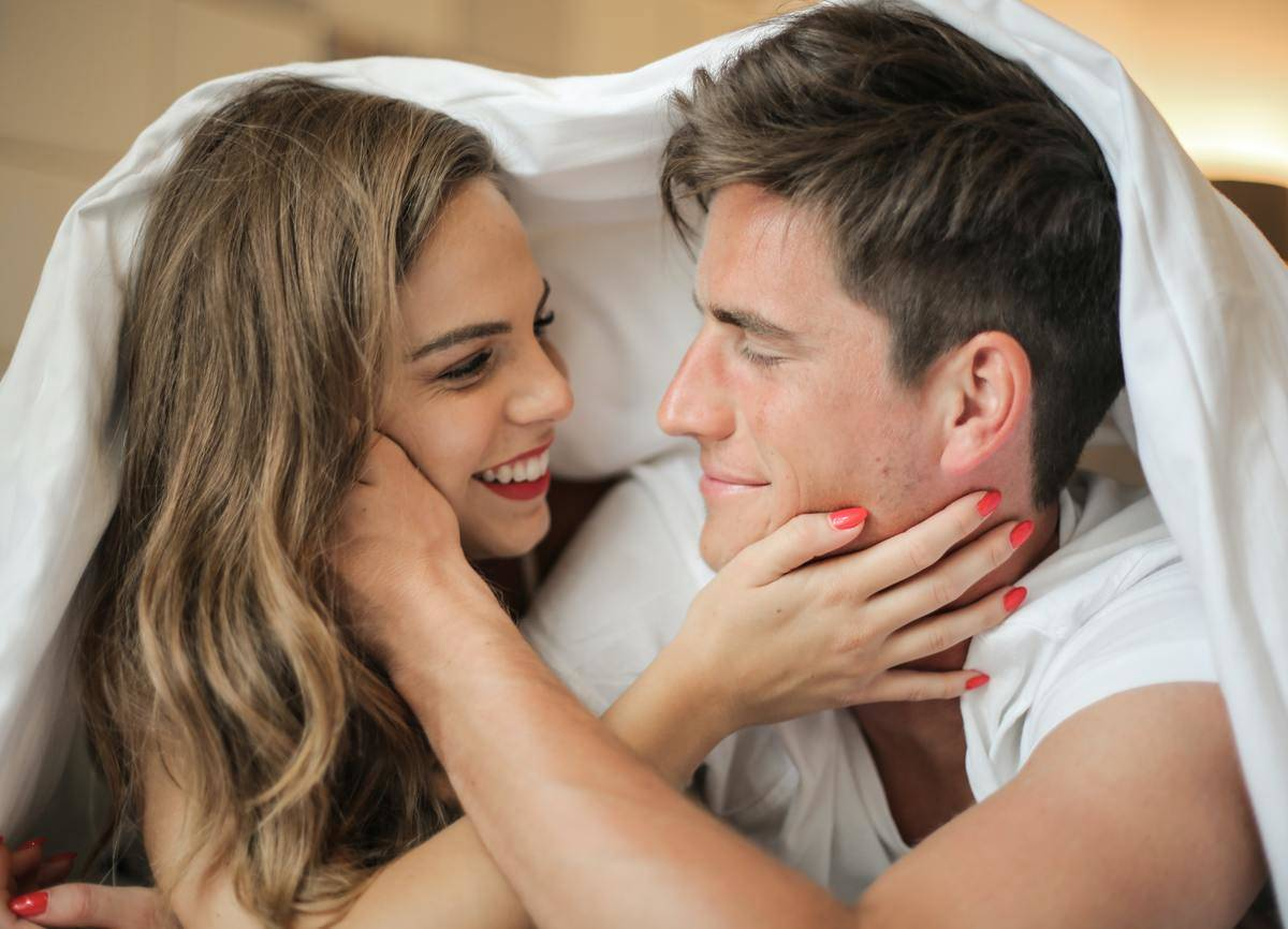 woman and man under bedsheet looking at each other
