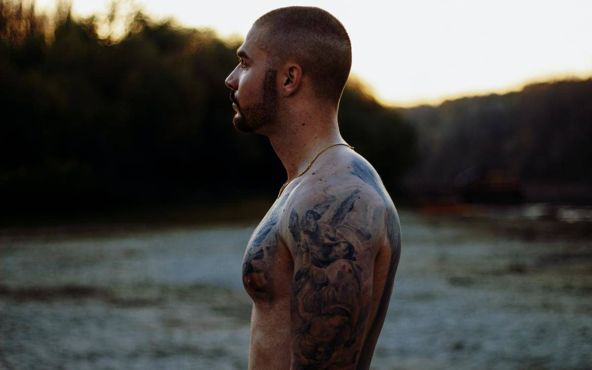 shirtless man stands outside covered in tattoos