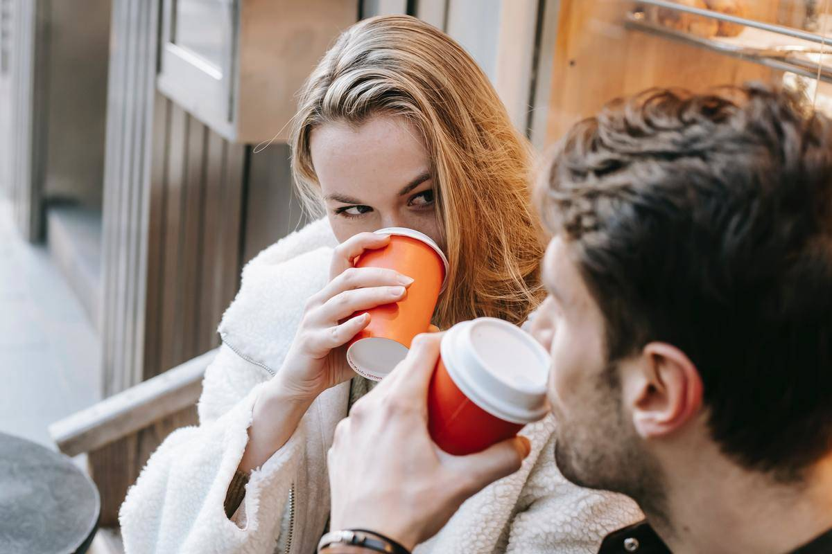a couple sitting outside drinking from coffee cups