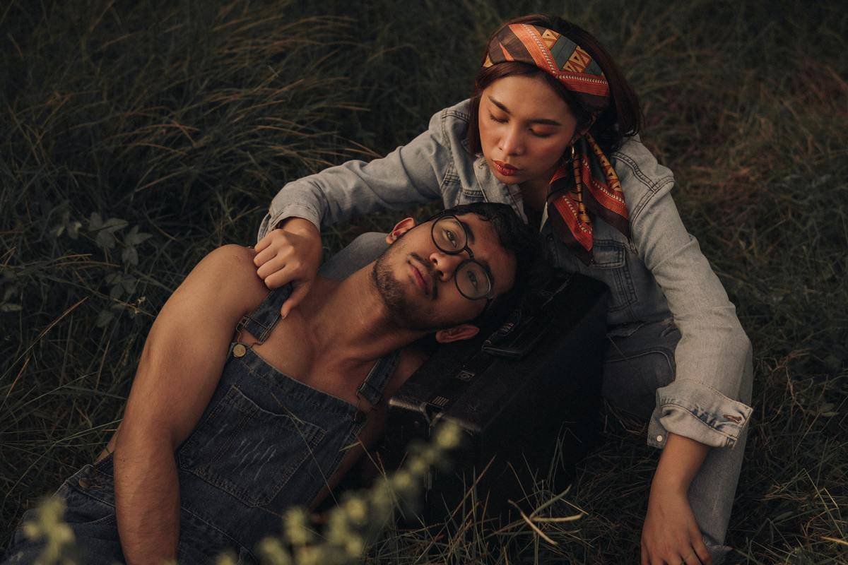 a couple sitting in some grass. He has his head on her lap