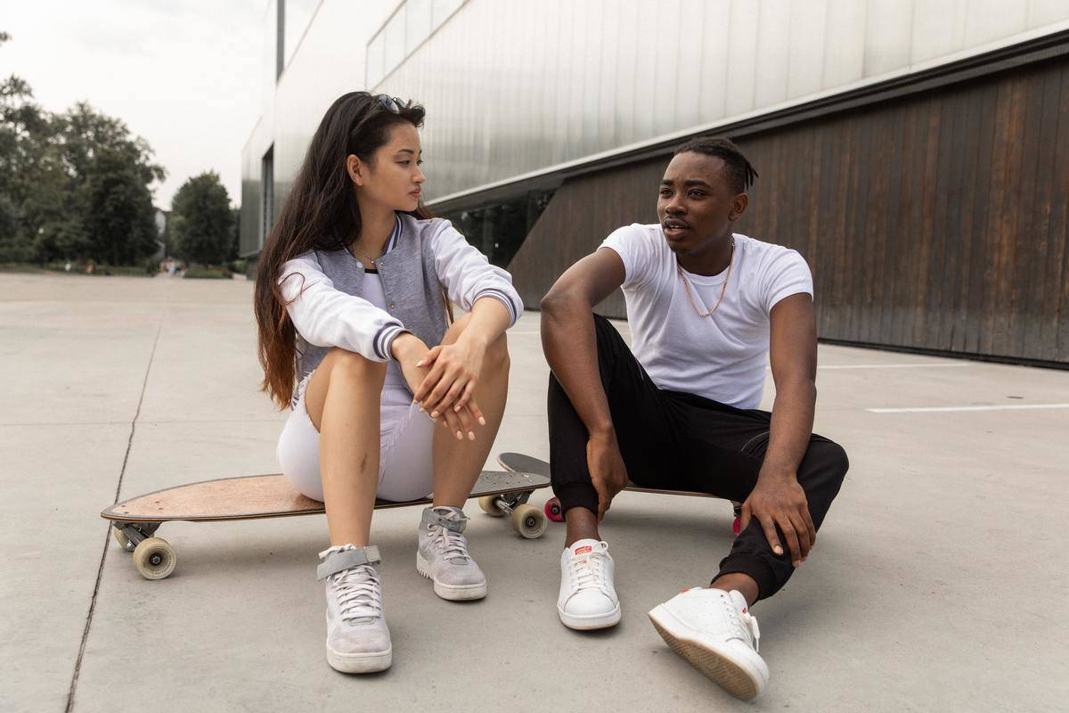 couple sitting on the ground with a skateboard