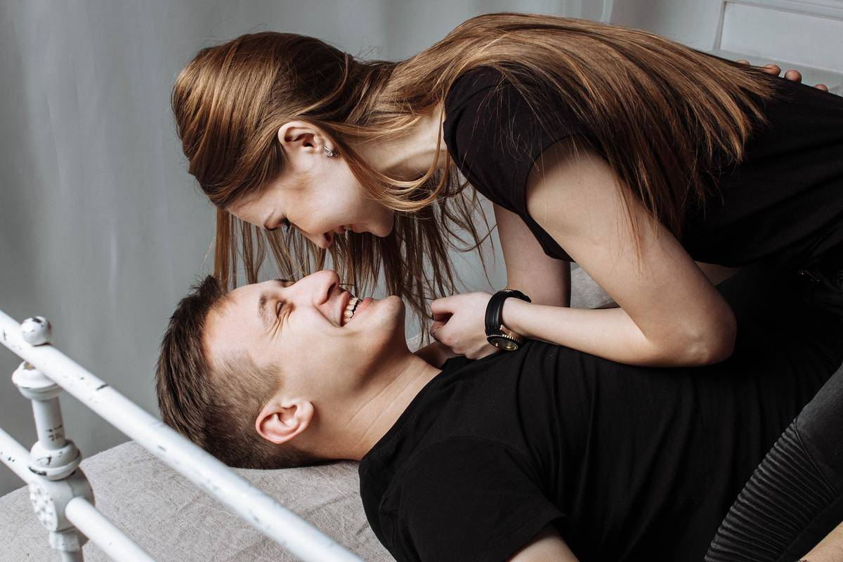 woman on top of man on bed, both smiling