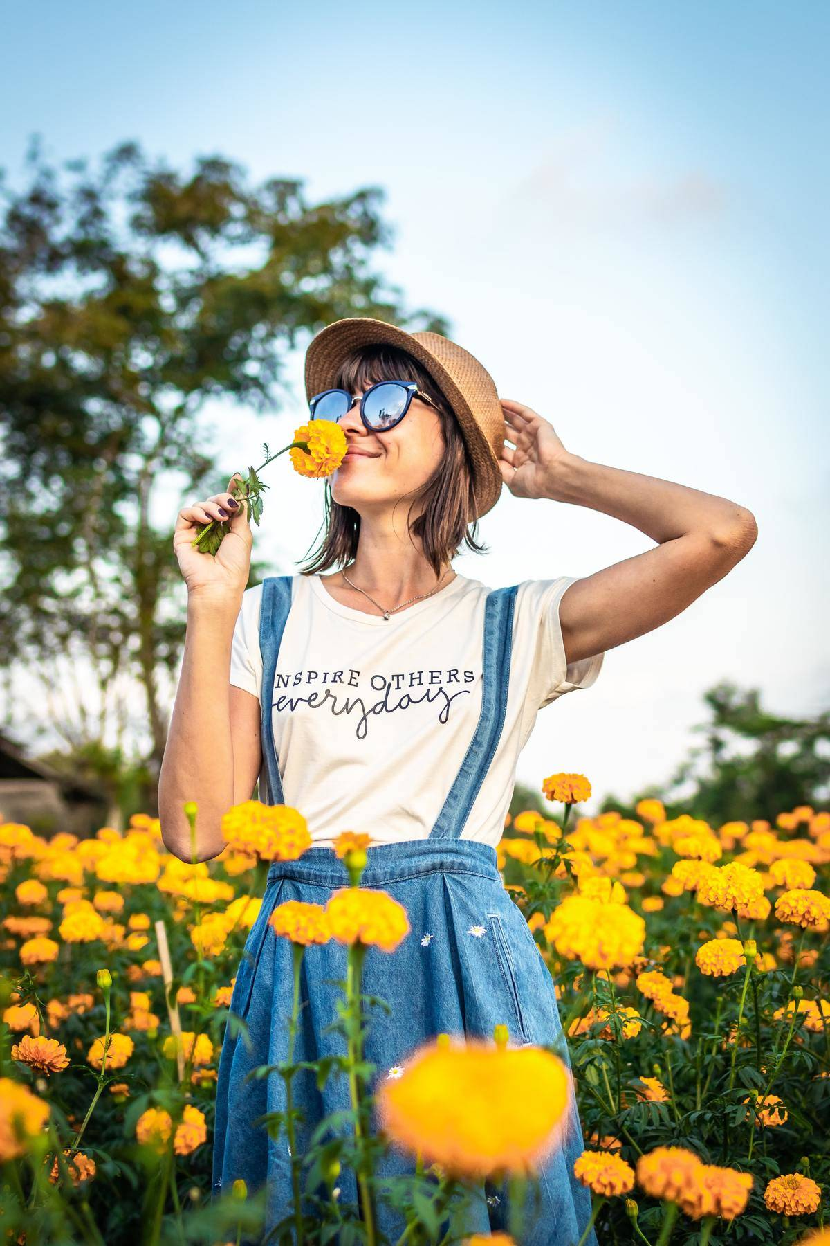 woman standing in a field smelling some flowers