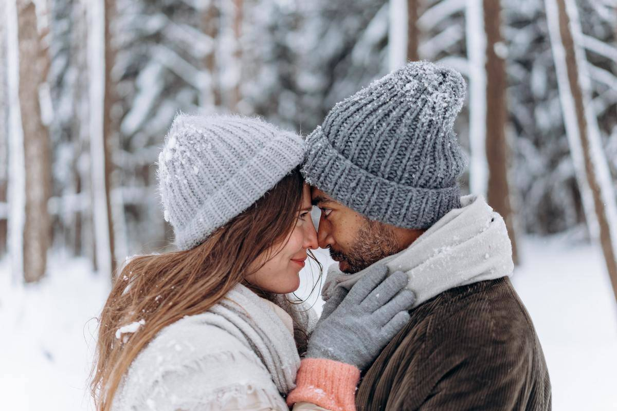 couple looking at each other intensely with winter hats and gloves on