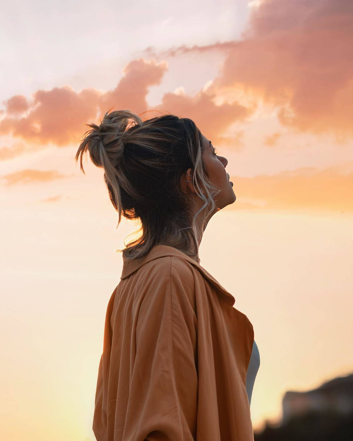 woman looking up at a sunset
