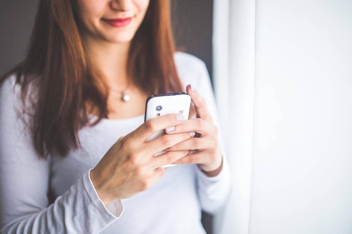 woman looking down at phone screen, texting