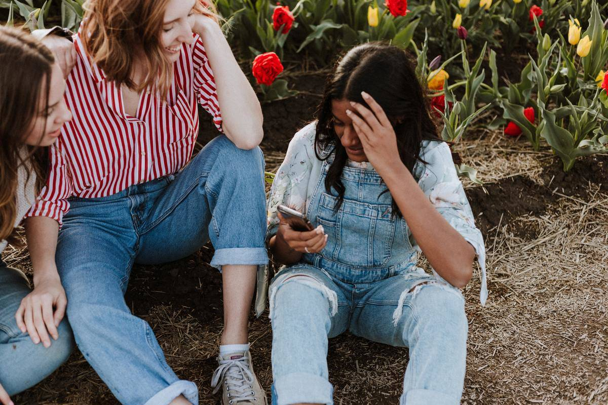 group of three women all in denim seated in flower field one woman looking down at phone