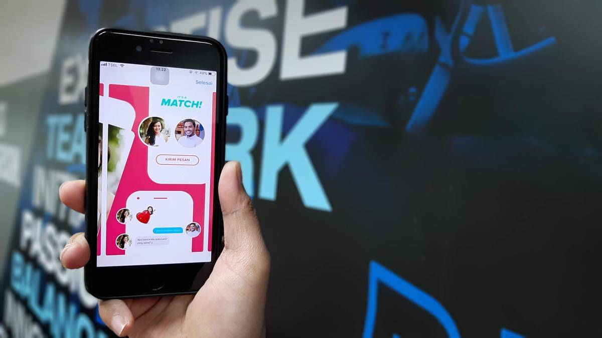 phone screen shows someone getting a match on Tinder