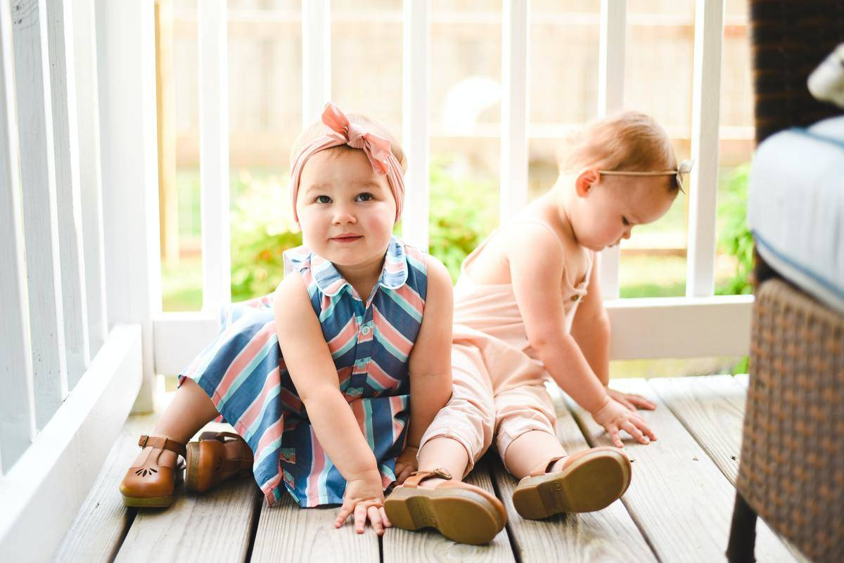 toddlers sitting on front porch and smiling