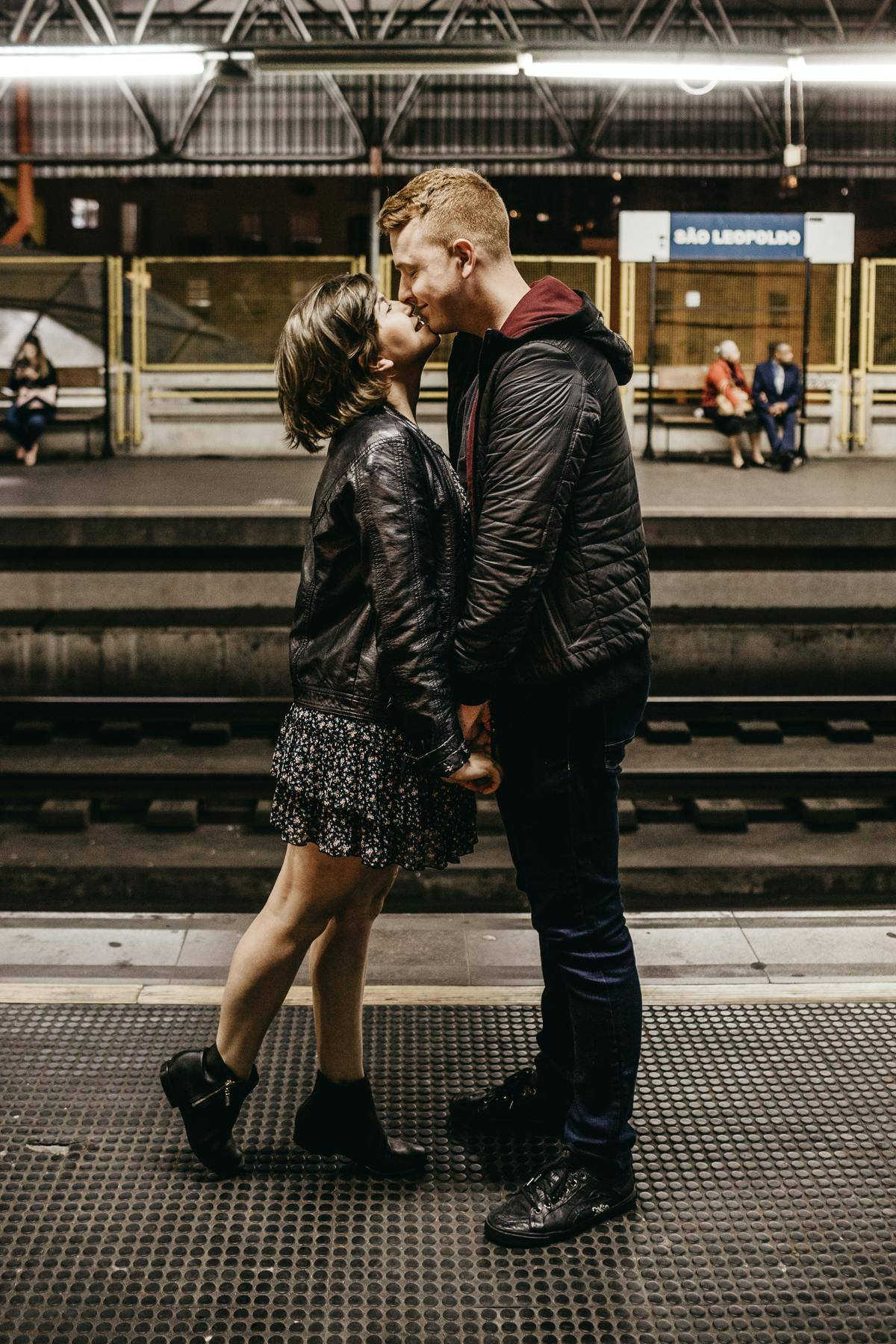 couple kissing on a train platform