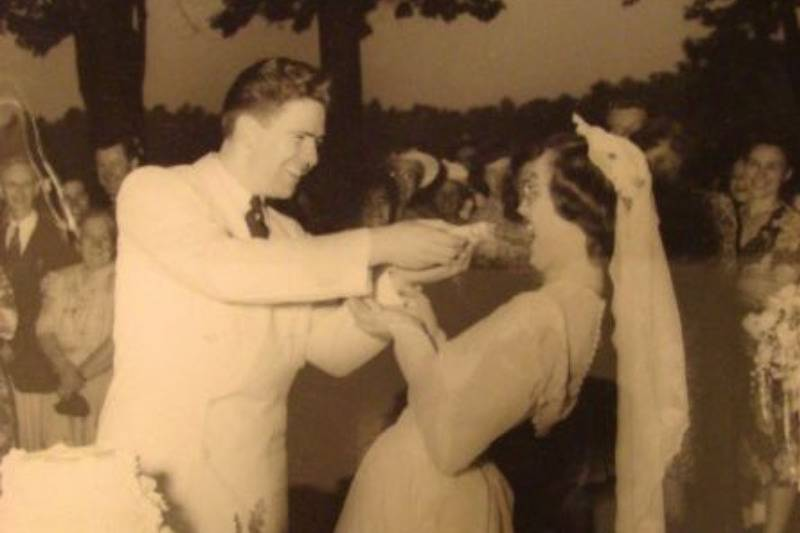 vintage wedding photo of groom feding cake to bride