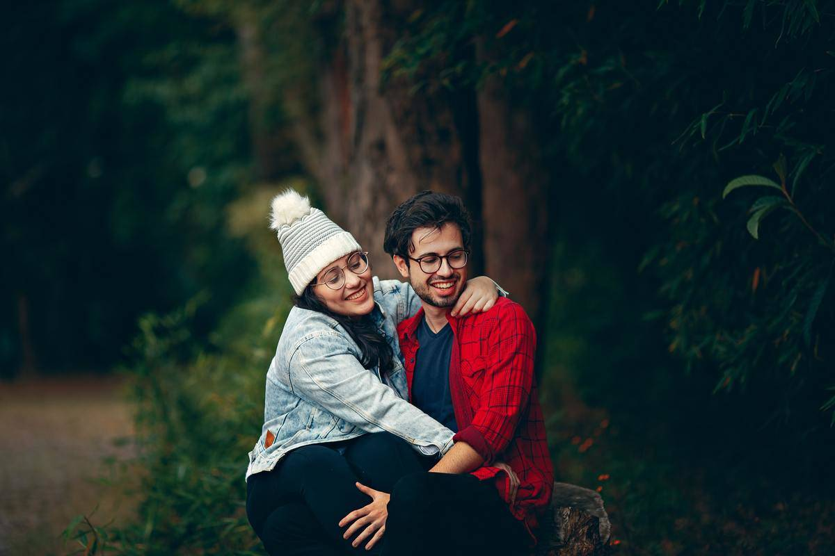 couple sitting outside laughing near a forest