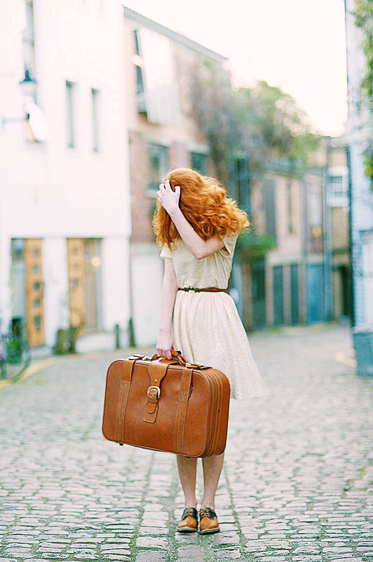 woman carrying luggage on pebble street